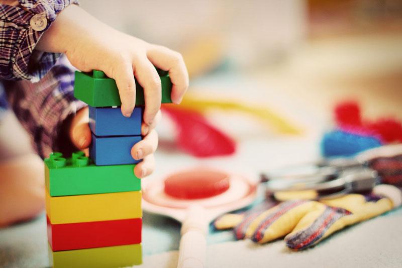 Kind spielt mit Bauklötzen als Symbol für mehr Geld für die Gemeinden im Bereich der Kindertagesstätten