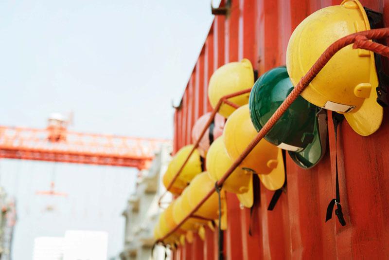Helme vor einem Baukontainer als Symbol für Infrastrukturentwickelung