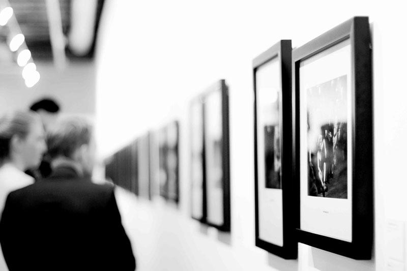 Einige Galleriebesucher vor einer schwarzweißen Bilderwand als Symbol für kulturelle Vielfalt