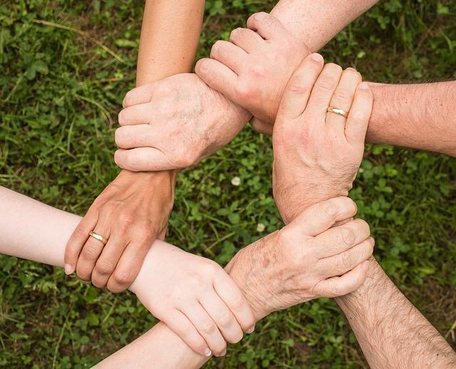 Mehrere über Kreuz greifende Hände als Symbol für Zusammenhalt und Ehrenamt